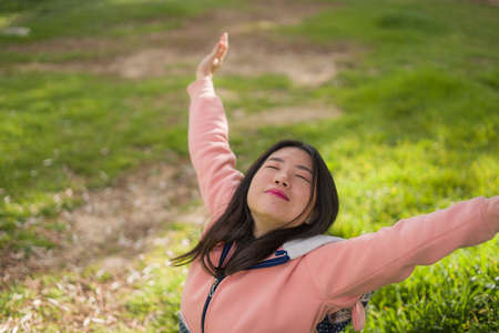 lifestyle portrait of young happy and beautiful Asian Korean woman in pink sweater lying on green grass cheerful and excited playing outdoors enjoying carefree Standard-Bild