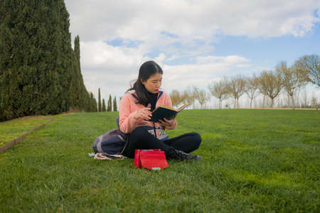 young Asian woman enjoying novel on grass - lifestyle portrait of young happy and pretty Chinese girl reading a book at beautiful city park in reading and studying concept