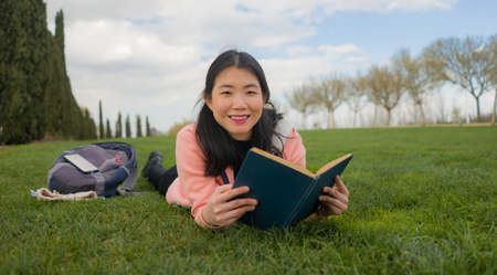 young Asian woman enjoying novel on grass - lifestyle portrait of young happy and pretty Korean girl reading a book at beautiful city park in reading and studying concept Reklamní fotografie