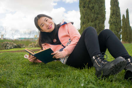 young Asian woman enjoying novel on grass - lifestyle portrait of young happy and pretty Japanese girl reading a book at beautiful city park in reading and studying concept