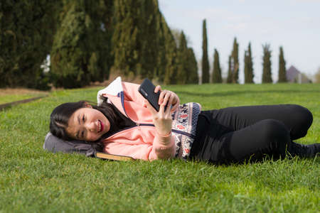 young happy Asian woman in city park - outdoors lifestyle portrait of  cheerful and pretty Korean girl taking selfie with mobile phone relaxed and playful on green grass