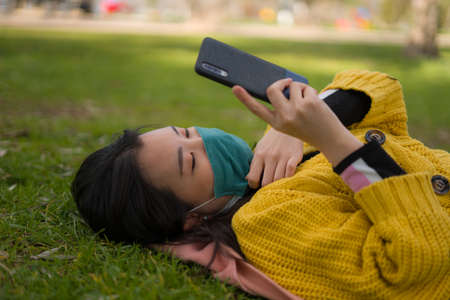 young Asian woman in city park  - outdoors lifestyle portrait of happy and pretty Chinese girl in face mask using internet with mobile phone relaxed on green grass
