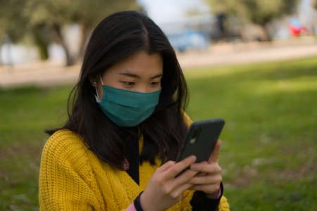 young Asian woman in city park  - outdoors lifestyle portrait of happy and pretty Korean girl in face mask using internet with mobile phone relaxed on green grass