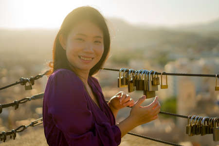 romantic lifestyle portrait of young happy and beautiful Asian Korean woman on sunset at love padlocks attached to city railing smiling cheerful Reklamní fotografie