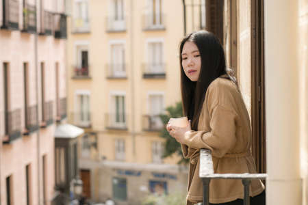 Asian woman in balcony thinking - outdoors lifestyle portrait of young beautiful and thoughtful Korean girl at drinking morning coffee looking to street indrawn and self-absorbed