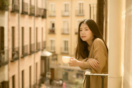 Asian woman in balcony thinking - outdoors lifestyle portrait of young beautiful and thoughtful Japanese girl at drinking morning coffee looking to street indrawn and self-absorbed