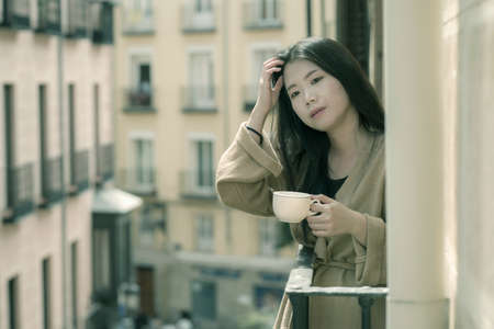 Asian woman in balcony thinking - outdoors lifestyle portrait of young beautiful and thoughtful Chinese girl at drinking morning coffee looking to street indrawn and self-absorbed