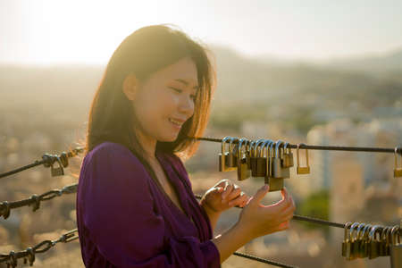 romantic lifestyle portrait of young happy and beautiful Asian Chinese woman on sunset at love padlocks attached to city railing smiling cheerful Reklamní fotografie