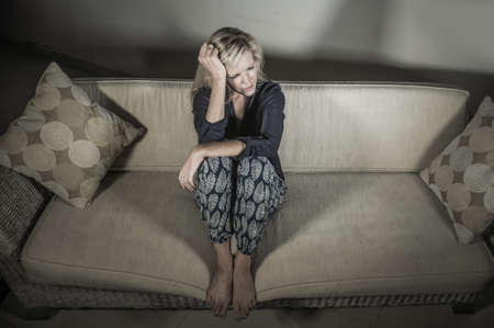 beautiful 40s woman depressed at home - dramatic portrait of sad and desperate blonde girl on couch suffering depression problem and anxiety crisis feeling helpless and lonely Banco de Imagens