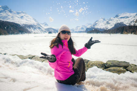 Chinese woman enjoying amazing snowy landscape view - happy and beautiful Asian girl playing with snow in front of frozen lake and mountains during Swiss Alps Winter holiday