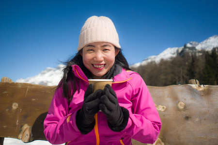 freezing Winter holidays - young happy and beautiful Asian Chinese woman on bench at frozen lake and snow mountains drinking coffee or hot chocolate enjoying Swiss Alps Banco de Imagens