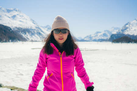 young Chinese woman enjoying amazing snowy landscape view - happy and beautiful Asian girl playful in front of frozen lake and snow mountains during Swiss Alps holiday