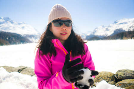 Korean woman enjoying amazing snowy landscape view - young happy and beautiful Asian girl playing with snow in front of frozen lake and mountains during Swiss Alps holiday Banco de Imagens