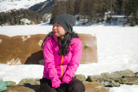 freezing Winter holidays - young happy and beautiful Asian Chinese woman on bench at frozen lake landscape surrounded by snow mountains enjoying Swiss Alps getaway Imagens