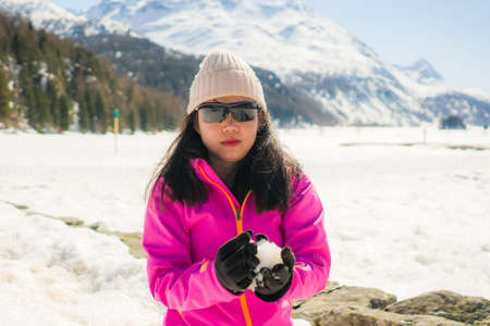 Chinese woman enjoying amazing snowy landscape view - happy and beautiful Asian girl playing with snow in front of frozen lake and mountains during Swiss Alps holiday