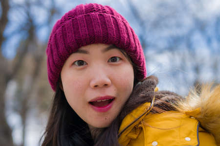 Christmas holidays in the snow - young beautiful and happy Asian Korean woman enjoying outdoors at cold mountain village enjoying Swiss Alps vacation