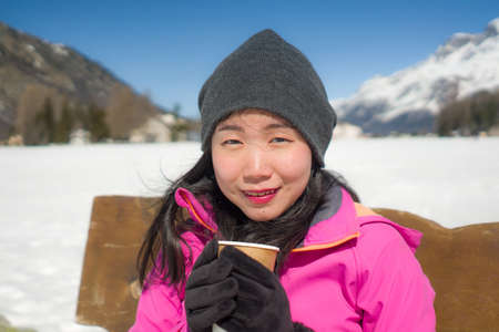 freezing Winter holidays - young happy and beautiful Asian Chinese woman on bench at frozen lake and snow mountains drinking coffee or hot chocolate enjoying Swiss Alps Imagens