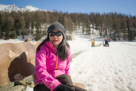 freezing Winter holidays - young happy and beautiful Asian Chinese woman on bench at frozen lake landscape surrounded by snow mountains enjoying Swiss Alps getaway Banco de Imagens