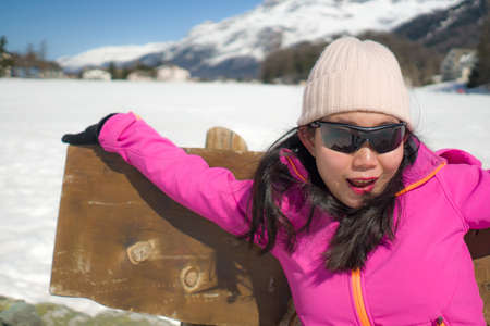 freezing Winter holidays - young happy and beautiful Asian Japanese woman on bench at frozen lake landscape surrounded by snow mountains enjoying Swiss Alps getaway Banco de Imagens