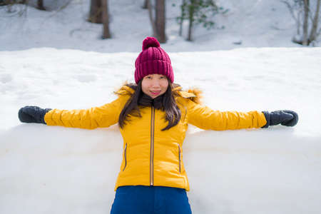 Christmas holidays in the snow - young beautiful and happy Asian Chinese woman enjoying outdoors at cold mountain village enjoying Swiss Alps vacation Imagens