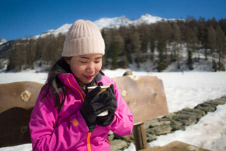 freezing Winter holidays - young happy and beautiful Asian Japanese woman on bench at frozen lake and snow mountains drinking coffee or hot chocolate enjoying Swiss Alps
