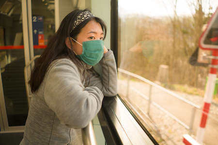 train travel during covid19 - young happy and cute Asian Japanese woman in face mask traveling on railcar enjoying landscape through the window