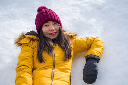 Christmas holidays in the snow - young beautiful and happy Asian Chinese woman enjoying outdoors at cold mountain village enjoying Swiss Alps vacation Banco de Imagens