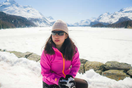 young Chinese woman enjoying amazing snowy landscape view - happy and beautiful Asian girl playing with snow in front of frozen lake and mountains during Swiss Alps holiday