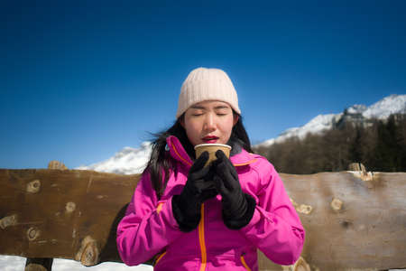 freezing Winter holidays - young happy and beautiful Asian Korean woman on bench at frozen lake and snow mountains drinking coffee or hot chocolate enjoying Swiss Alps