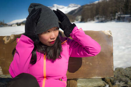 freezing Winter holidays - young happy and beautiful Asian Korean woman on bench at frozen lake landscape surrounded by snow mountains enjoying Swiss Alps getaway Banco de Imagens