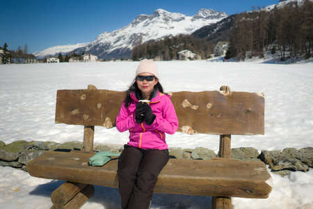 freezing Winter holidays - young happy and beautiful Asian Korean woman on bench at frozen lake landscape surrounded by snow mountains enjoying Swiss Alps getaway Imagens