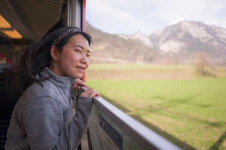 train travel getaway - lifestyle portrait of young happy and beautiful Asian Chinese woman traveling on railway looking through window relaxed and cheerful