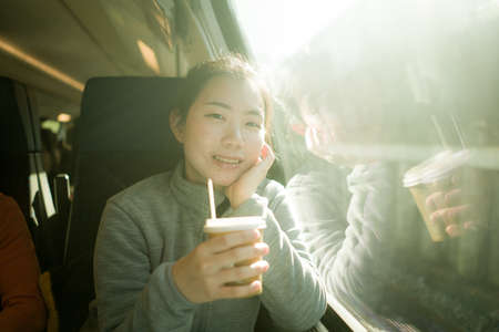 lifestyle portrait of young happy and beautiful Asian Chinese woman traveling on train looking through window drinking coffee