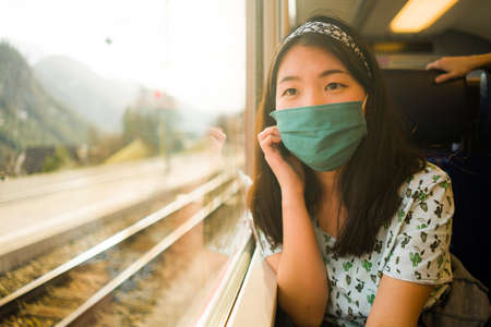 train travel in times of covid19 - young happy and cute Asian Korean woman in face mask traveling on railcar looking landscape through the window enjoying holiday getaway Stock Photo