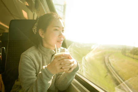 train travel getaway - lifestyle portrait of young happy and beautiful Asian Japanese woman traveling on railway looking through window  drinking coffee