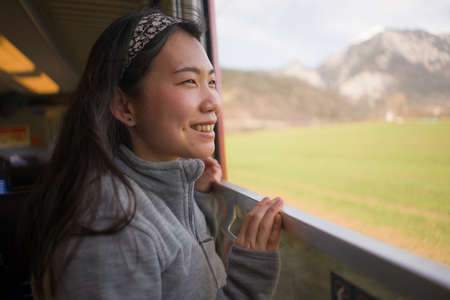 train travel getaway - lifestyle portrait of young happy and beautiful Asian Korean woman traveling on railway looking through window