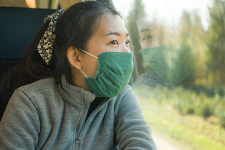 train travel during covid19 - young happy and cute Asian Japanese woman in face mask traveling on railcar enjoying landscape through the window Stock Photo