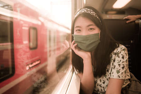 train travel in times of covid19 - young happy and cute Asian Chinese woman in face mask traveling on railcar looking landscape through the window enjoying holiday getaway