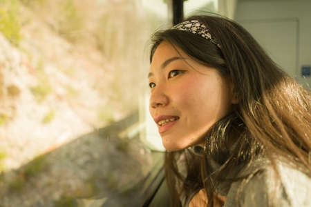 train travel getaway - lifestyle portrait of young happy and beautiful Asian Korean woman traveling on railway looking through window relaxed and cheerful