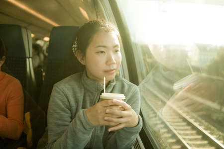 train travel getaway - lifestyle portrait of young happy and beautiful Asian Korean woman traveling on railway looking through window  drinking coffee