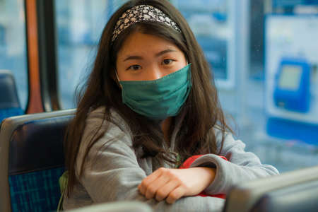 urban lifestyle during covid19 - young pretty and sweet Asian Chinese woman with mask and backpack traveling on tram railcar in Europe