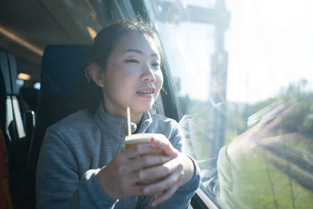 train travel getaway - lifestyle portrait of young happy and beautiful Asian Chinese woman traveling on railway looking through window  drinking coffee