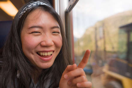 train travel getaway - lifestyle portrait of young happy and beautiful Asian Japanese woman traveling on railway looking through window relaxed and cheerful