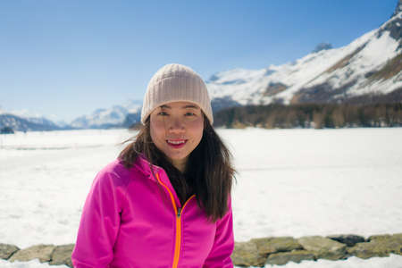 winter holidays at snow mountains - young happy and beautiful Asian woman enjoying cheerful the beauty of frozen lake and snowy landscape at Swiss Alps