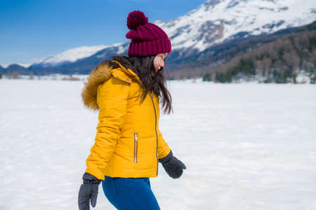 winter lifestyle portrait of young happy and attractive Asian Japanese woman at beautiful snow mountains landscape enjoying Easter holidays in Swiss Alps