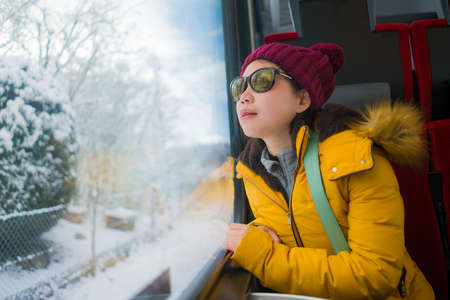 train travel getaway - young happy and beautiful Asian Japanese woman enjoying snow landscape through railcar window during Winter holiday trip