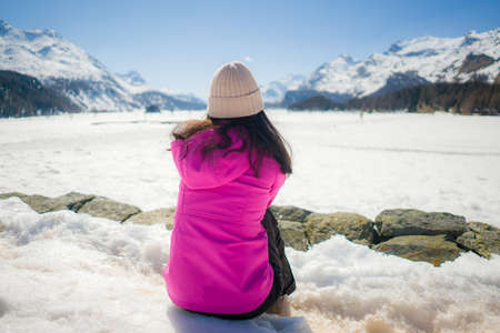 woman enjoying amazing snowy landscape view - back of girl in winter jacket sitting in front of frozen lake and snow mountains enjoying Swiss Alps getaway