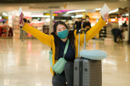 Asian woman flying in covid19 times - lifestyle portrait of young happy and pretty Japanese girl in face mask and yellow jacket waiting on airport lounge ready for holiday trip