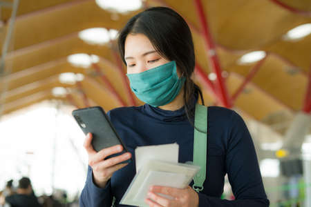 Asian woman flying in covid19 times - lifestyle portrait of young tired and attractive Korean girl in face mask waiting on airport checking her mobile phone