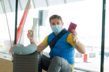 holiday travel and tourism - young happy and attractive man in face mask at airport departures lounge holding passport and boarding pass Фото со стока